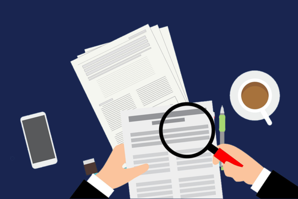 Graphic of person's hands holding paperwork and magnifying glass, with coffee and phone on desk - A-Z of internal audit Veritau