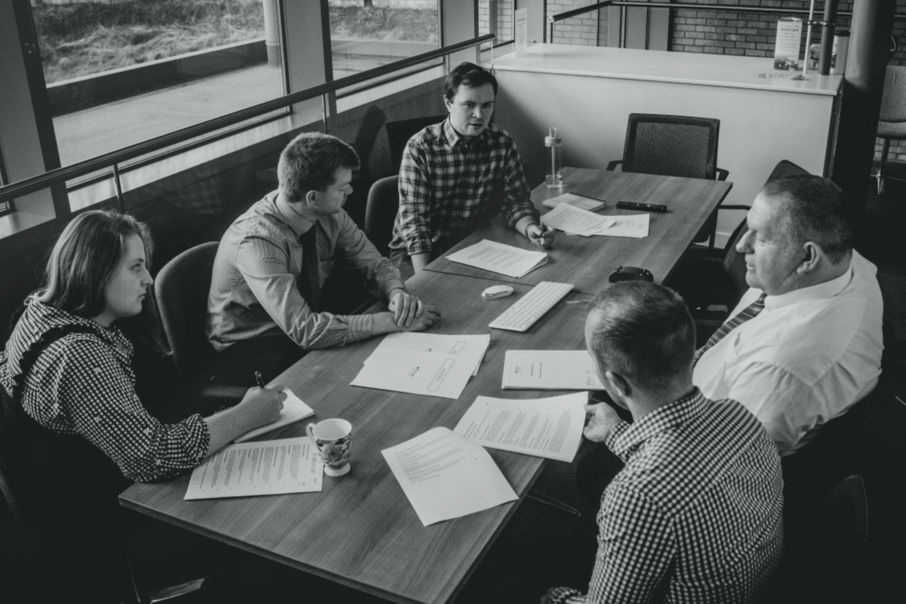 Image of five Veritau staff in meeting with papers on table - About Veritau, our company