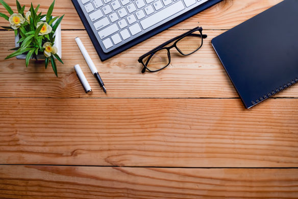 Office desk table with notebook, pen , glasses, keyboard and flower - IIA business risk survey