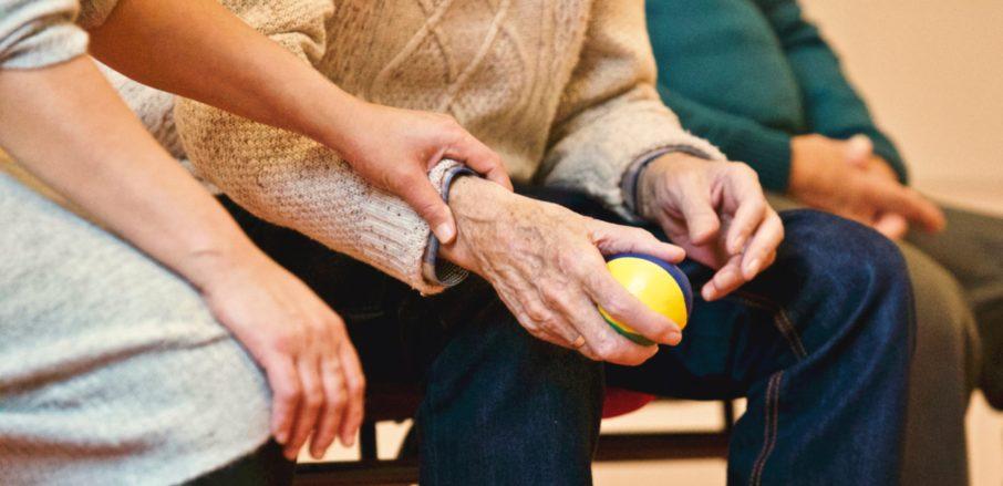Image of elderly persons hand being held by carer - social care fraud - Veritau