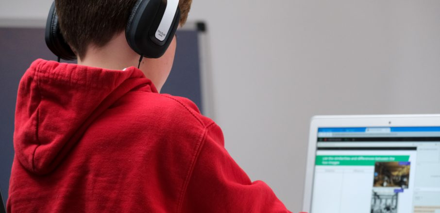 Children's internet code schools - Veritau - Child in red hoodie looking at internet content on laptop